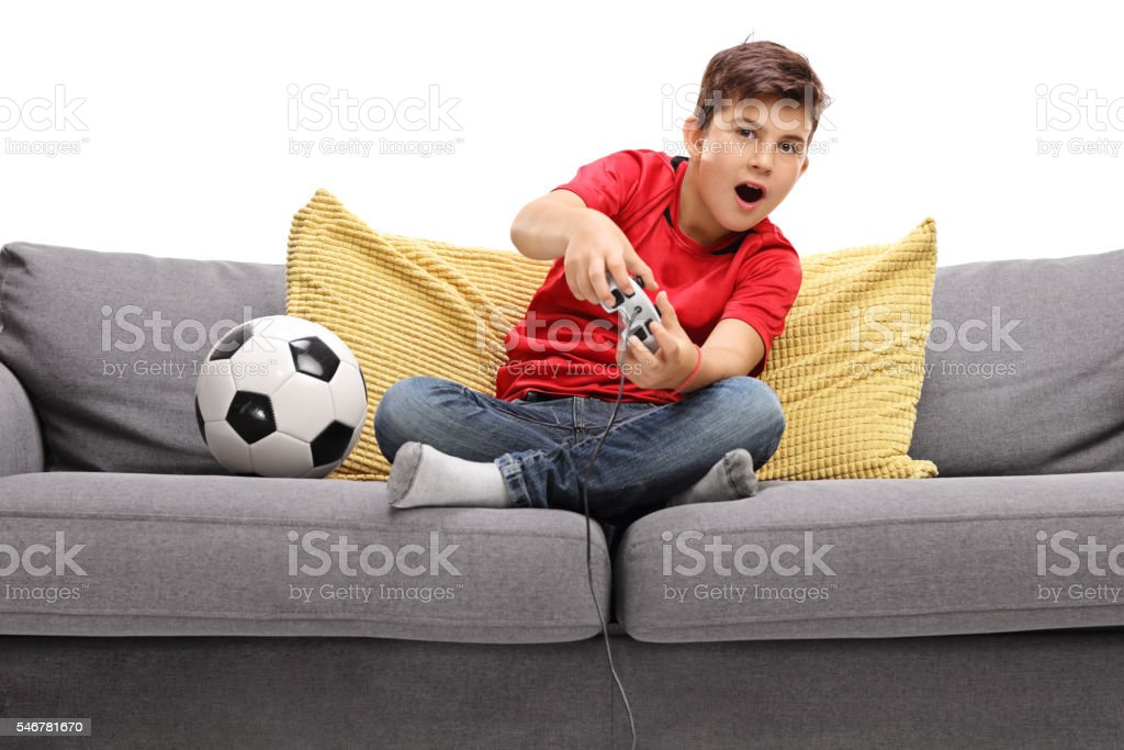 Boy playing football video game stock photo
