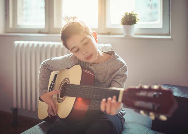 junge spielt gitarre wie zu hause fühlen. - one song training stock-fotos und bilder