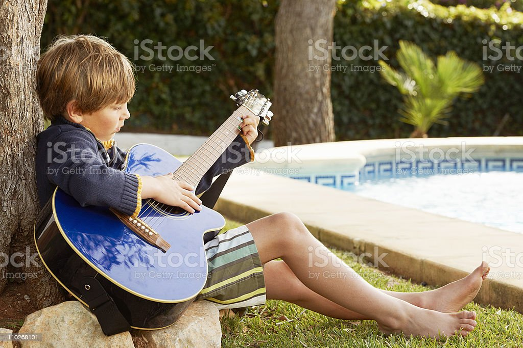 Ragazzo Suona la chitarra con piscina - foto stock