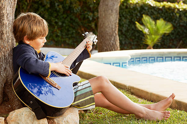 Boy playing guitar by pool stock photo