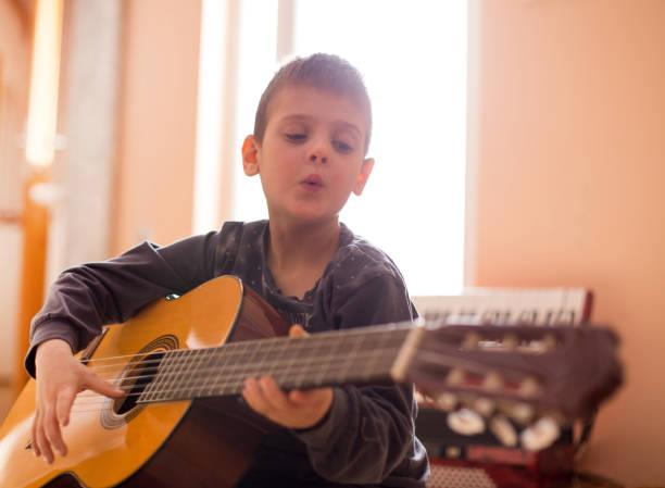 junge gitarre spielen - one song training stock-fotos und bilder