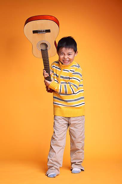 boy playing guitar - broken guitar stock photos and pictures