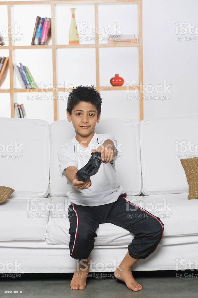 Boy playing handheld video game stock photo