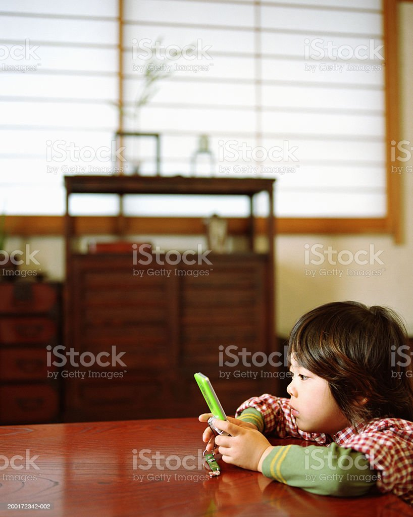 Boy (4-6) playing handheld video game, side view royalty-free stock photo