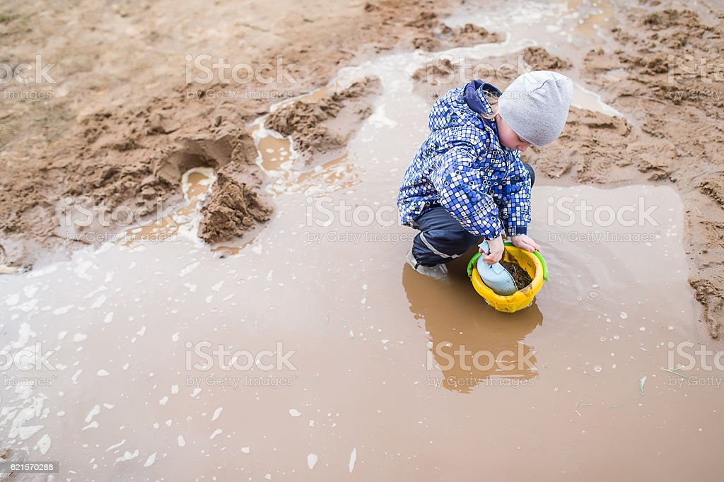 Boy playing in a muddy puddle photo libre de droits