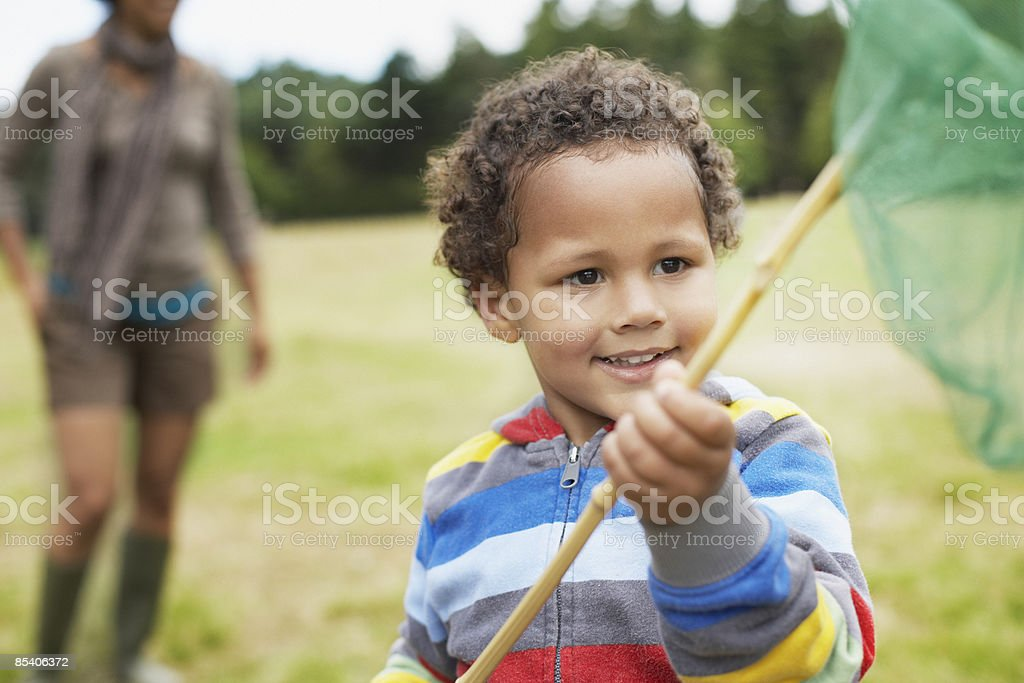 Boy playing in park with butterfly net royalty-free stock photo