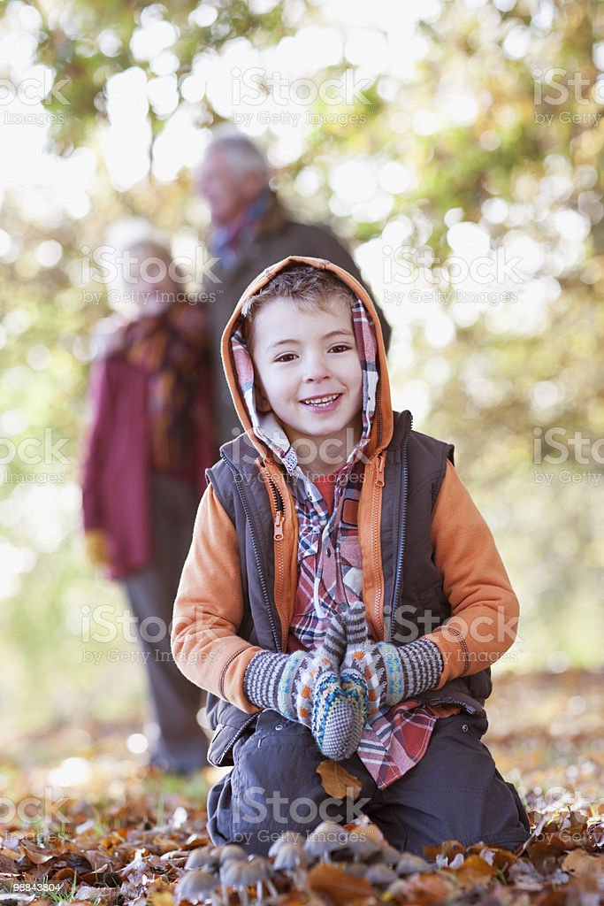 Boy playing in pile of autumn leaves 免版稅 stock photo