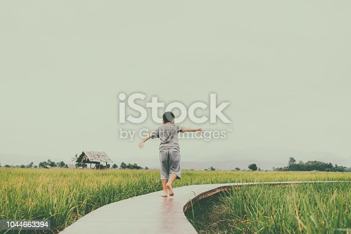 Asian boy playing in rice paddy in Thailand