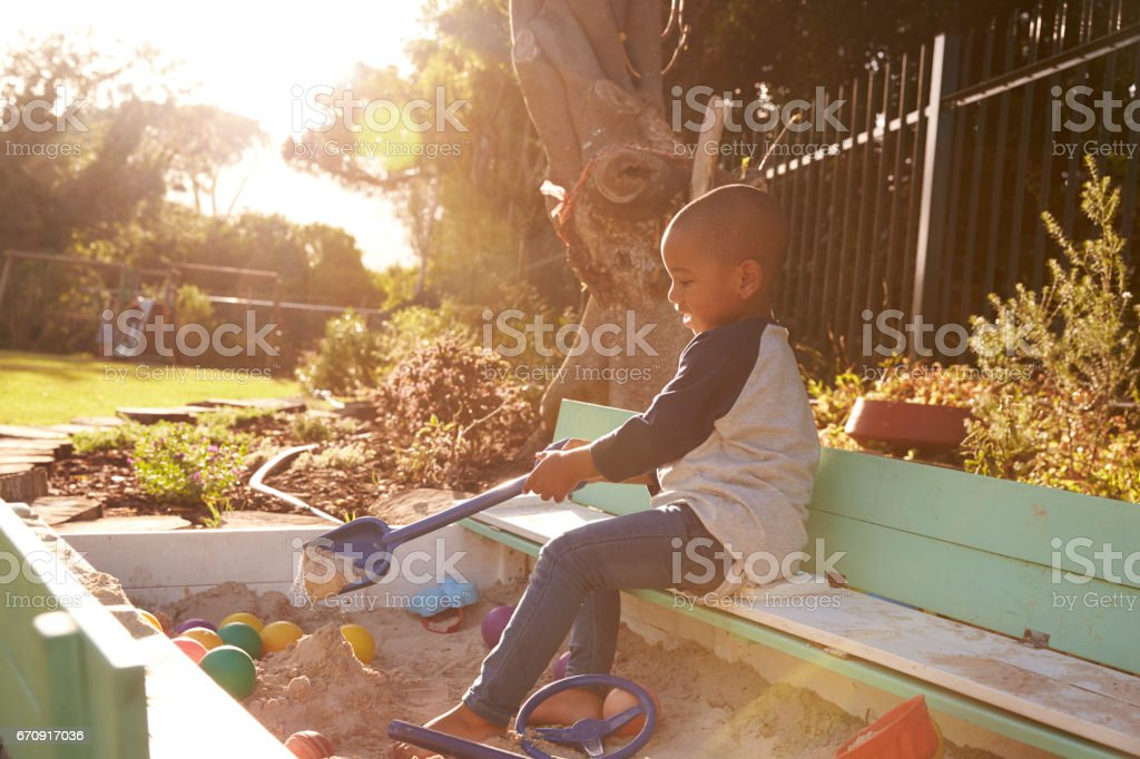 Boy Playing In Sand Box Outdoors In Garden stock photo