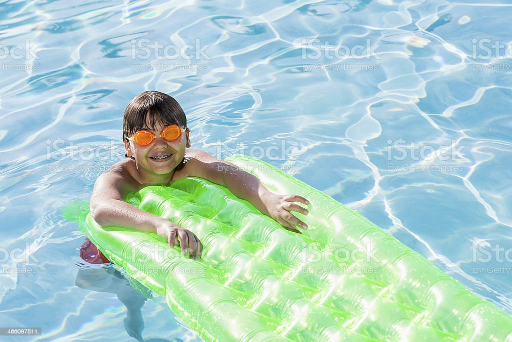 Boy playing in swimming pool. stock photo