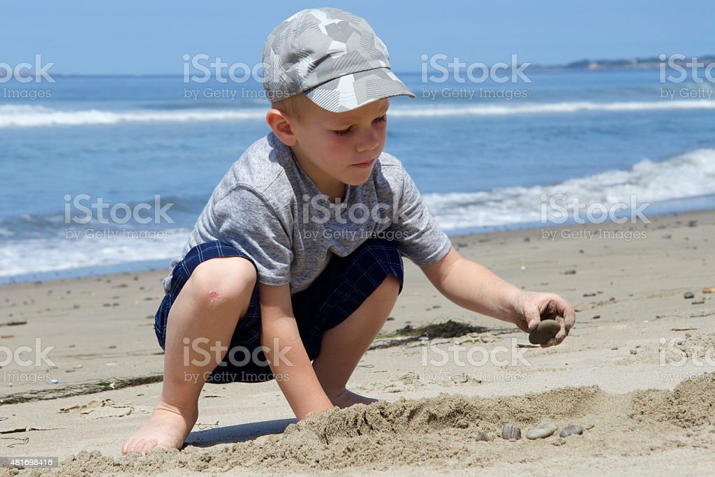 boy playing in the sand near the Pacific Ocean stock photo