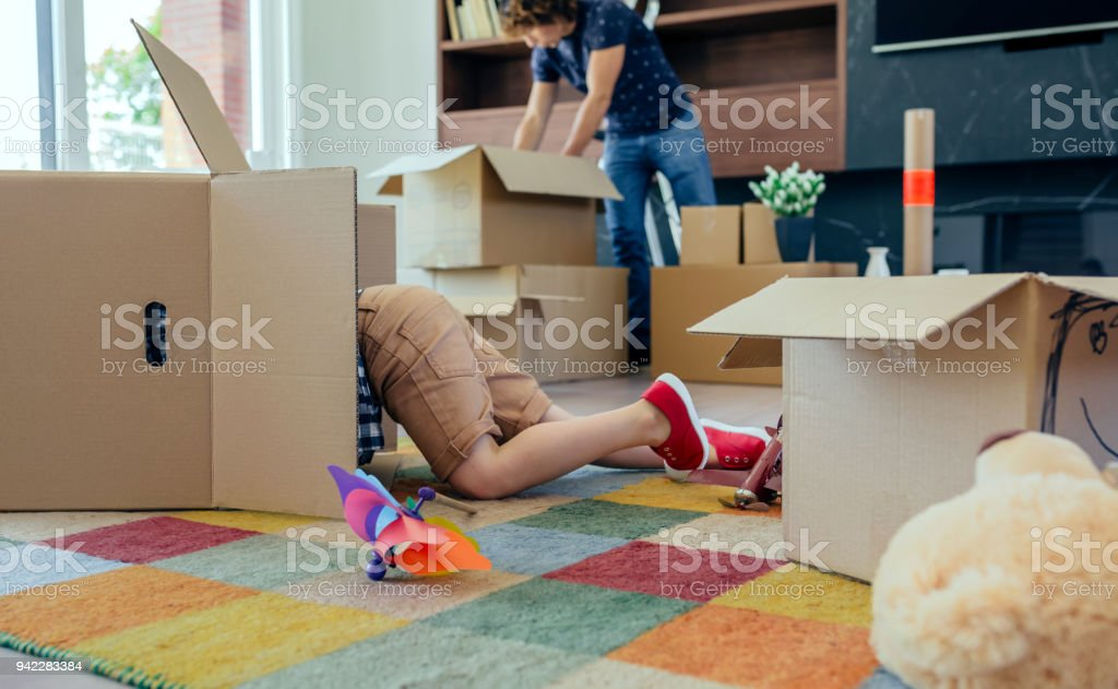 Little boy playing inside a moving box while his father unpacks in...