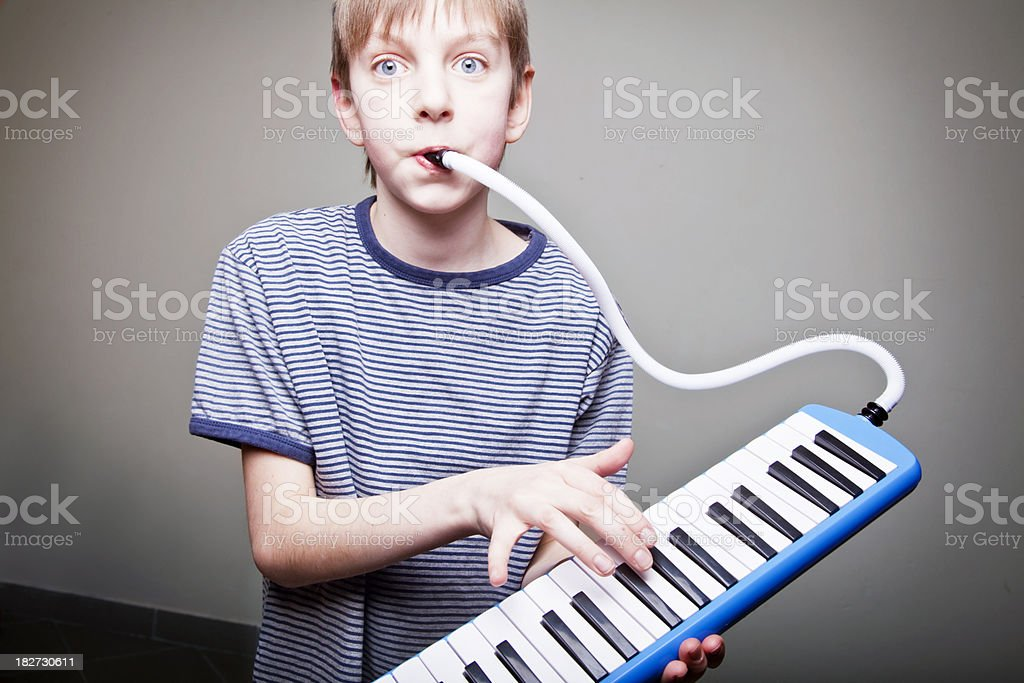 boy playing melodica stock photo