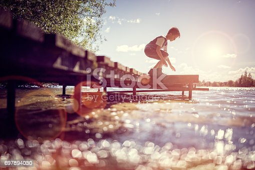Boy playing on a pier by lake on summer holiday vacation