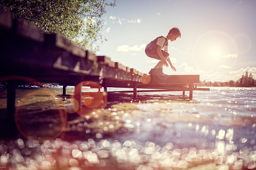 Boy playing on a pier by lake on summer vacation