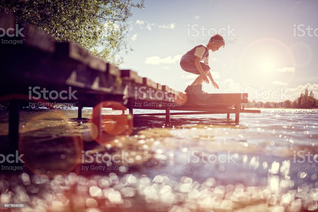 Boy playing on a pier by lake on summer vacation stock photo