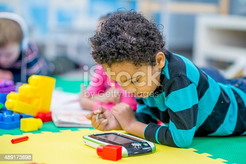 655532196 istock photo Boy Playing on Electronic Tablet 489173698