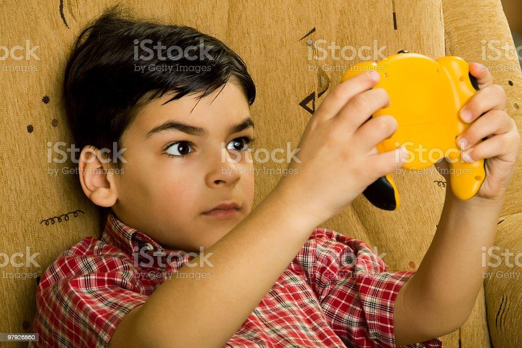 Boy playing on game-boy royalty-free stock photo