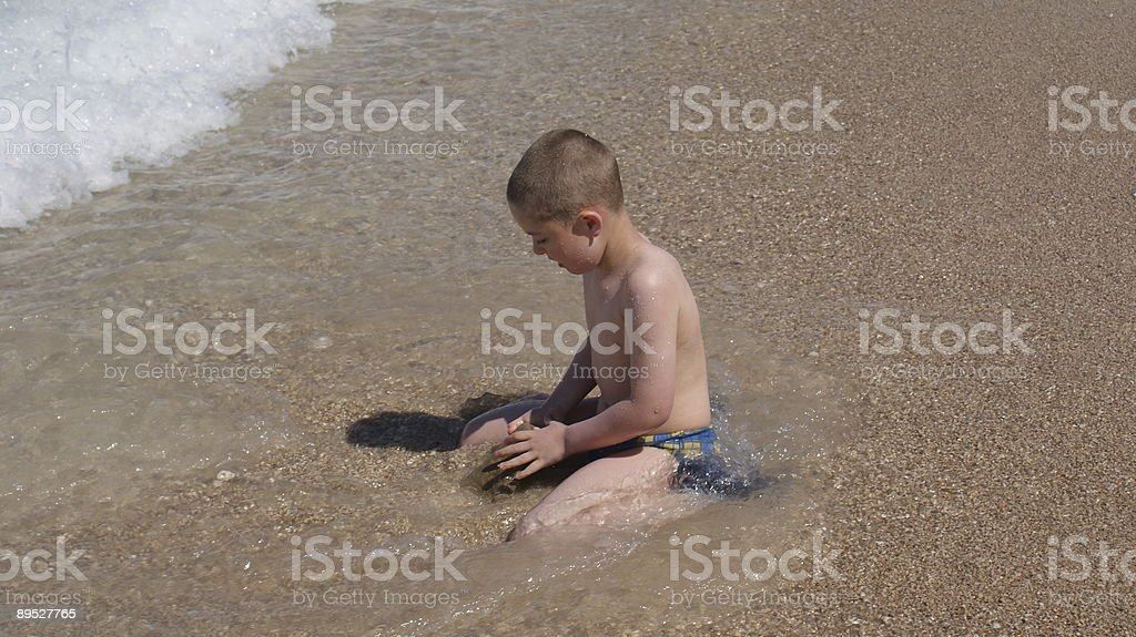 Boy playing on the beach royalty-free stock photo