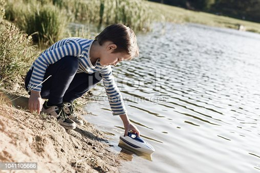 506991764istockphoto Boy playing on the lake with a toy boat 1041105666