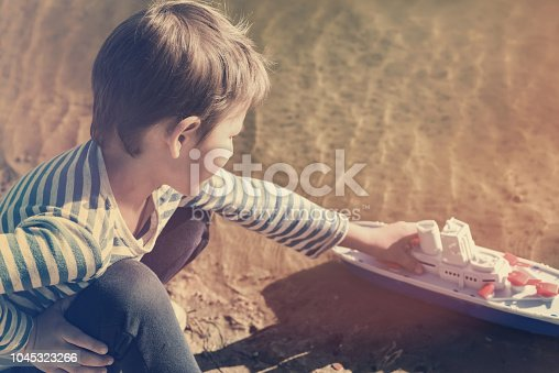 506991764istockphoto Boy playing on the lake with a toy boat 1045323266