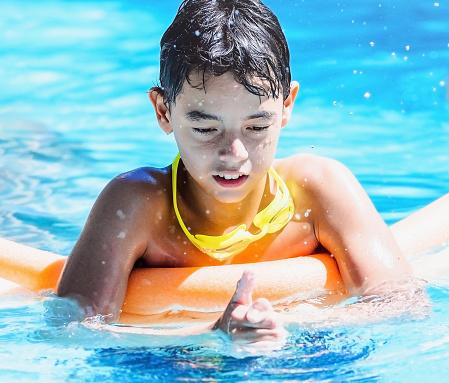 naked boy playing around pool
