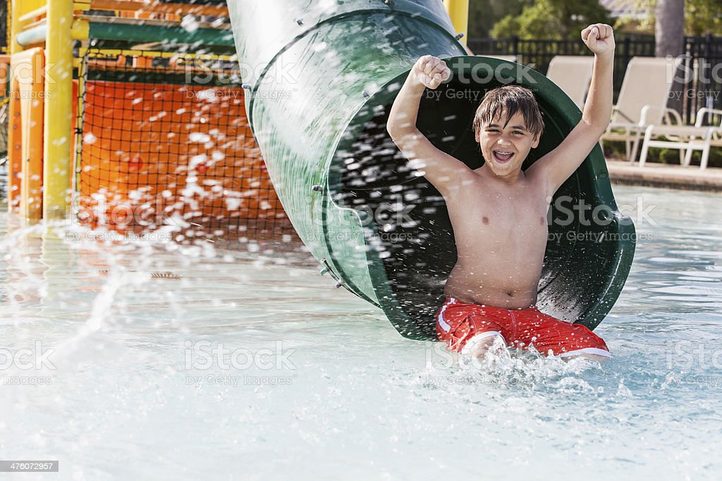 Boy playing on water slide stock photo