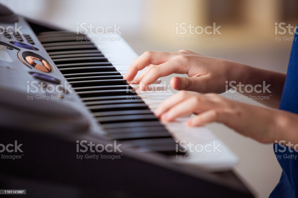 Boy playing piano in training class Midsection of boy playing piano. Male student is learning on keyboard instrument. He is sitting in music class. 12-13 Years Stock Photo