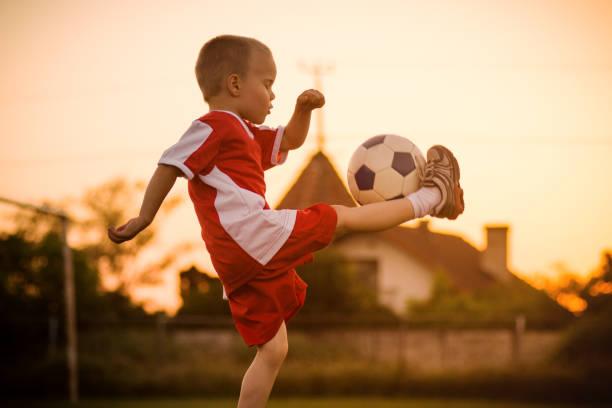 niño jugando fútbol - sepia imagen virada fotografías e imágenes de stock