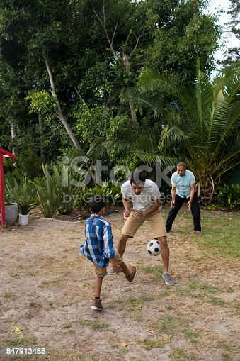 829627936istockphoto Boy playing soccer with parents on field 847913488