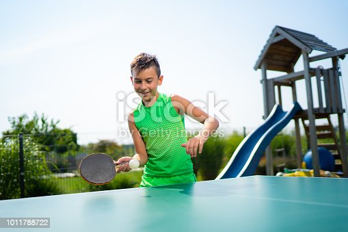 10 year od boy playing tabletennis table tennis pingpong ping pong in private garden during his summer holidays long vacation smiling