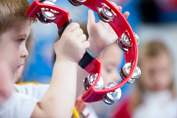 boy playing tambourine at nursery - musical instrument stock photos and pictures