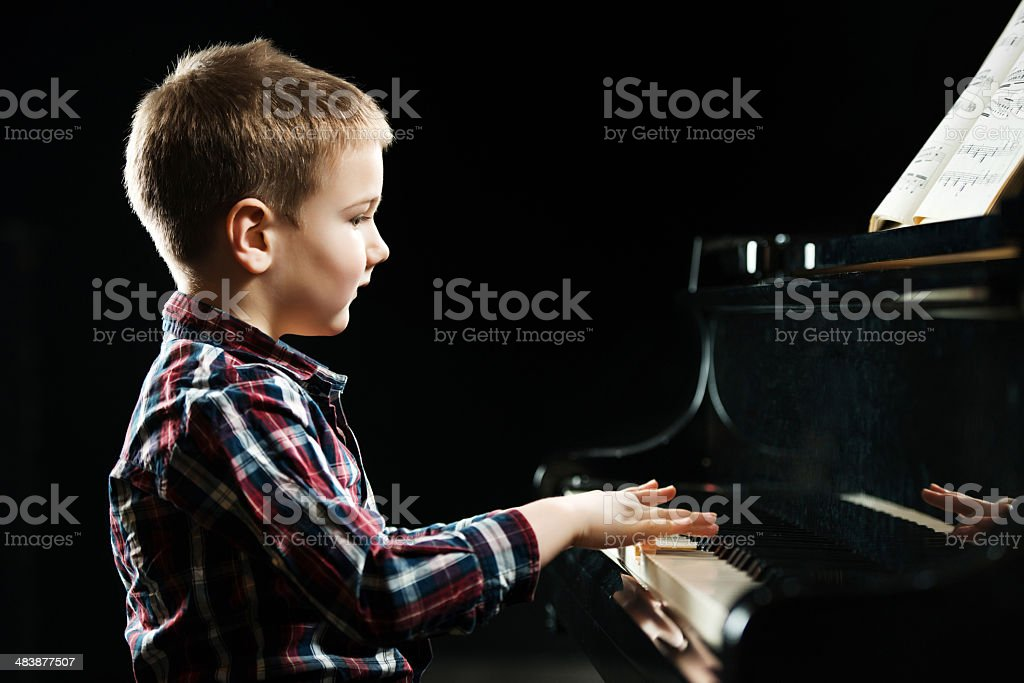 Boy playing the piano. royalty-free stock photo