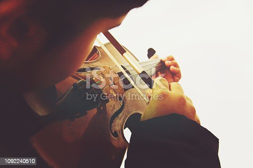 A boy playing the stringed and bowed musical instrument, the violin, captured from behind