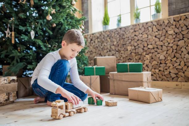 Junge Spielzeug Unter Weihnachtsbaum spielen. Hölzernes Auto mit kleinen Geschenken. – Foto