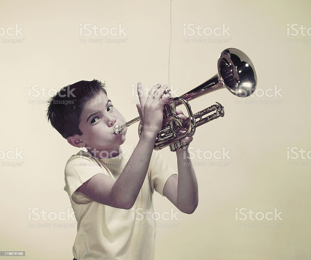 Boy playing trumpet, portrait stock photo