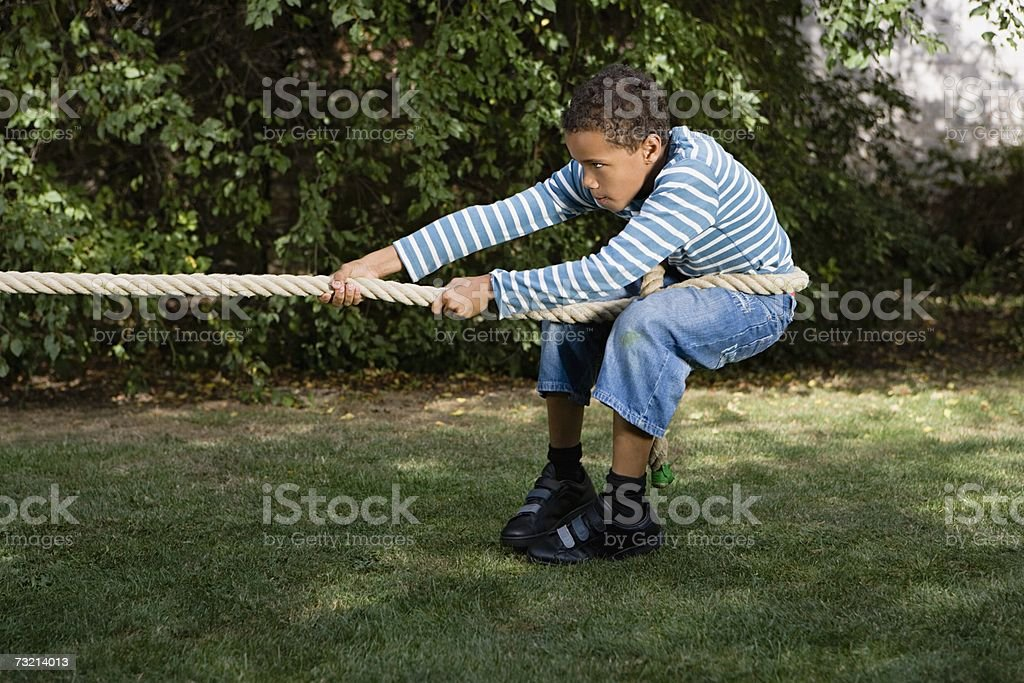 Boy playing tug of war royalty-free stock photo