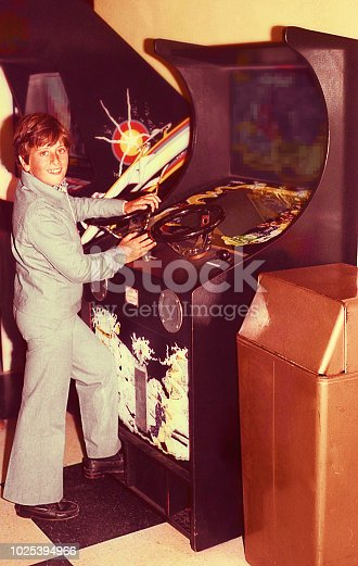 Vintage image of a boy playing in an old vide ogame machine.