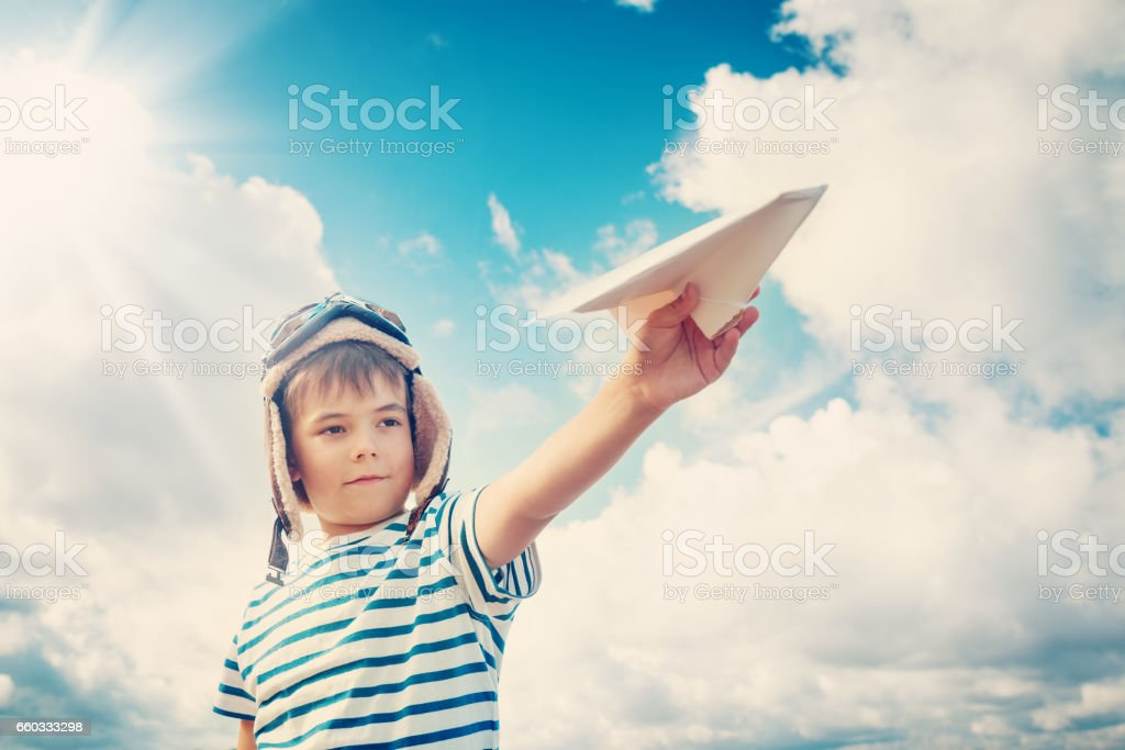 boy playing with a paper plane in aviator hat stock photo