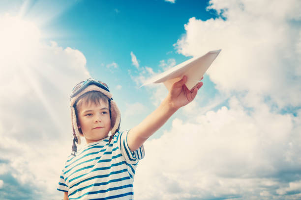 boy playing with a paper plane in aviator hat - paper airplane stock photos and pictures