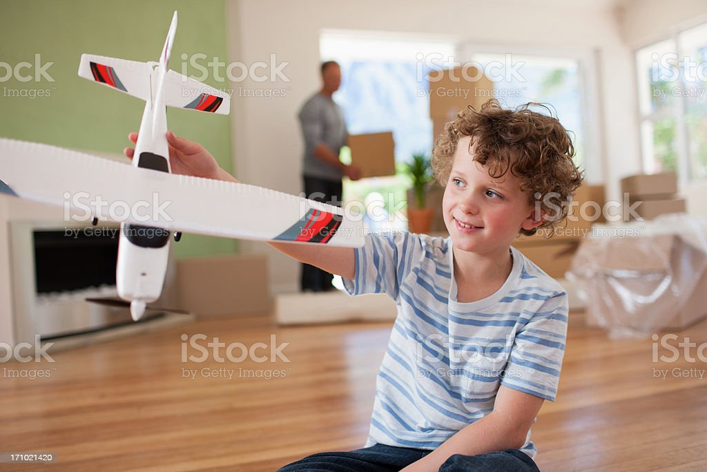 Boy playing with airplane in new home stock photo
