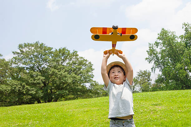 Boy playing with an airplane of toy in the park stock photo