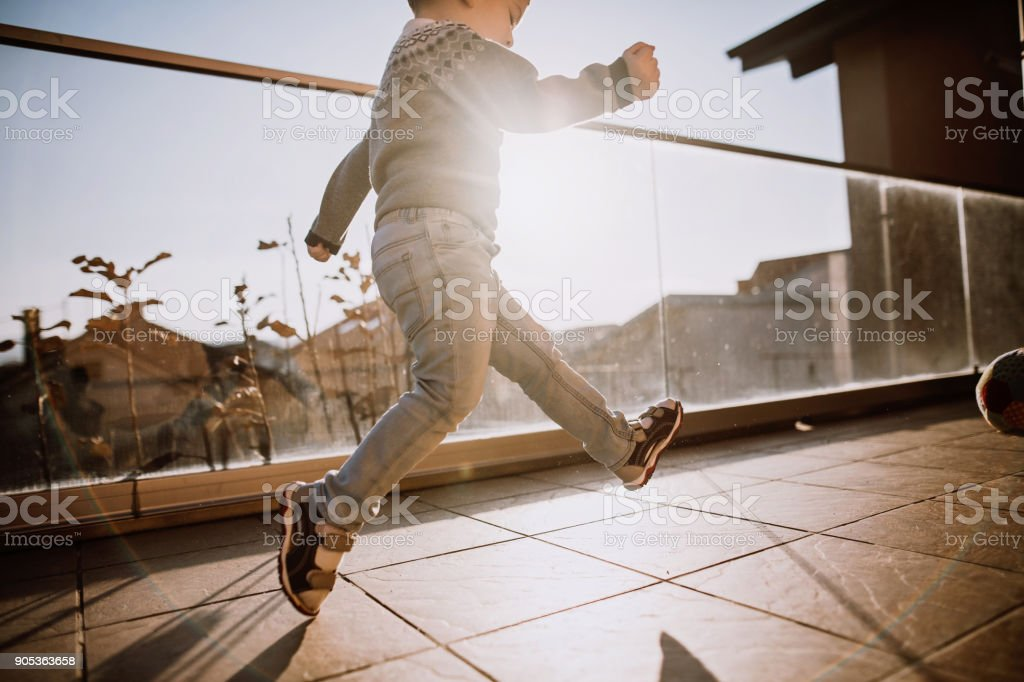Boy playing with ball on balcony stock photo