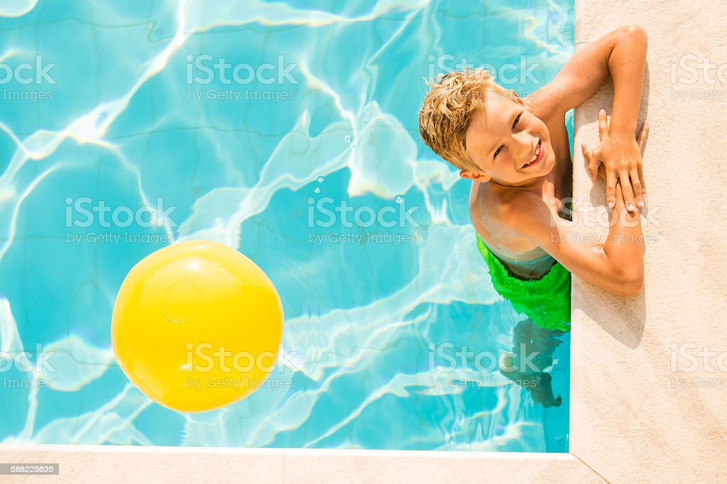 Boy (9 years) playing with beach ball in swimming pool - Photo