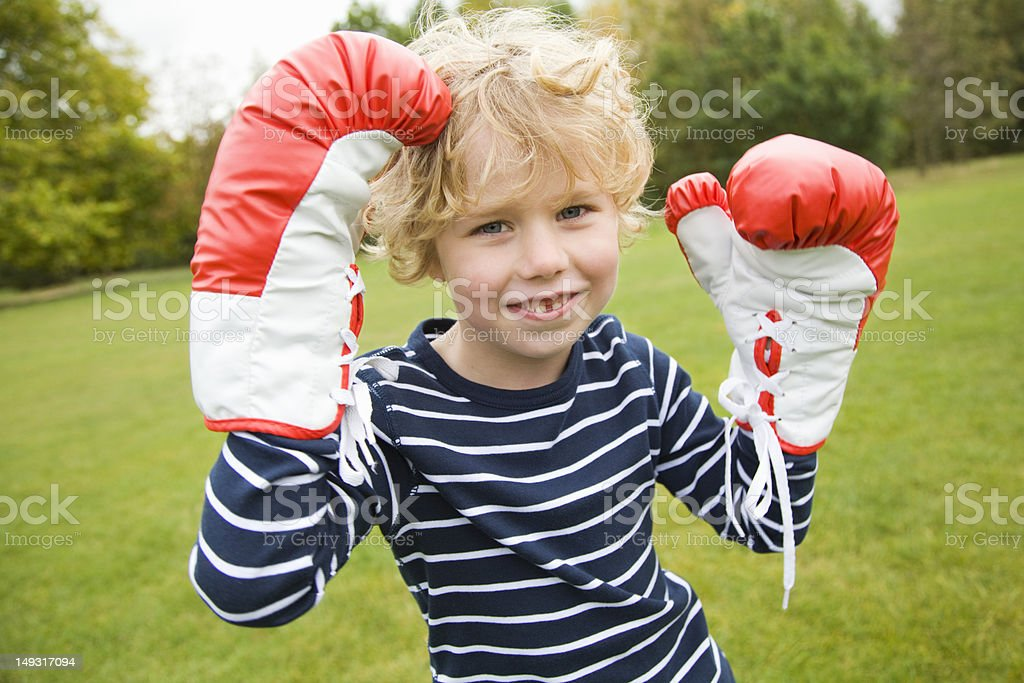 Boy playing with boxing gloves outdoors royalty-free stock photo