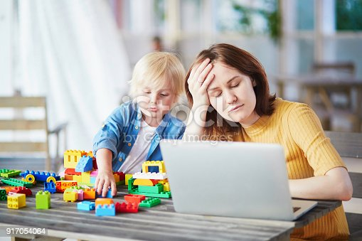 istock Boy playing with construction blocks while his mother working 917054064