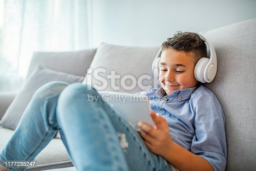 Smiling boy in big white headphones watching videos on tablet computer. Little boy in headphones is using a digital tablet and smiling. Concentrated kid playing with digital tablet