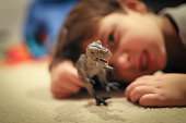Boy playing with dinosaur