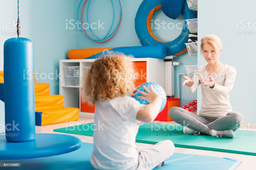 Boy playing with his therapist stock photo