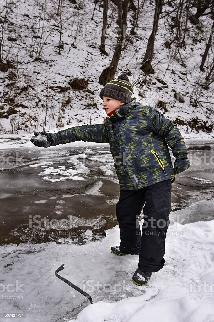 Boy playing with ice stock photo